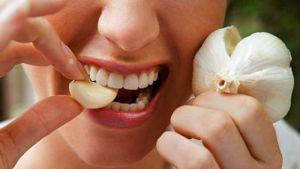 Девушка кушает чеснок