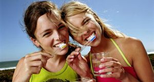 Девушки чистят зубы